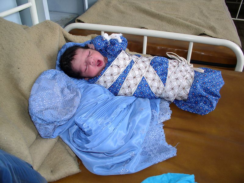 Baby lying on his mother's burqa