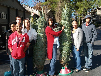 (Center) Monique Evans, Founder & President of Children's Pride presents Live Christmas trees to three deserving families in Roswell, Georgia.