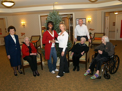 (L) to (R) Monique Evans, Founder & President of Children's Pride presenting a Live Christmas tree to Donna Branch, Activities Director at Sunrise Assisted Living Center as residents look on.