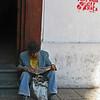 Senor reading paper outside San Francisco church