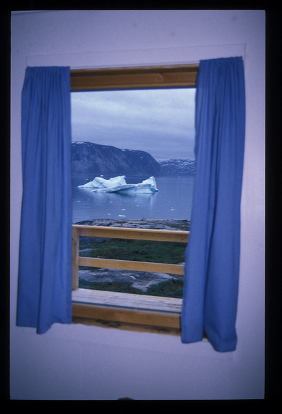 """The Arctic Hotel Ice Rock Bar in Ilullisat is the only bar I know with an iceberg view. Ice Rock rocked in cigarette smoke, late. High summer meant something up here. Happy hour was from 22:00 to 23:00. <br /> <br /> A drunken man pumped my hand so fervently when I told him where I was from he really made me glad to be American.  But I decided in the end he was just weary of the constant dribble of tourists from nowhere but Denmark. Sick 'o Danes.<br /> <br /> *****<br /> <br /> Rain this morning. We heard it on the window overnight, in our sleeping bags on our bunk beds in the Ataa barracks. All of the tourist wonders near Ataa were out of the question in this weather, and Silva was already scheming to pass us off onto the boatload of Germans so he wouldn't have to sail us back to Ilullisat. <br /> <br /> And so we did fall in with Willy, the captain of the German excursion, and his passengers and crew. Trouble was, they weren't bound for Ilullisat, but rather Rodebay. <br /> <br /> When Willy came into the yellow hut for coffee, Silva set upon him. His passengers would rather be in Ilullisat than Rodebay on a day like today, wouldn't they, and Willy told Silva that he'd have to ask them, but in any event he'd take us, so Silva waved off any other complications. <br /> <br /> *****<br /> <br /> By eleven we were at sea, ten of us, southbound in the rain, maybe for Ilullisat. Willy's boat was the Maya Qaqqaq, from Nuuk, built for twelve, and we all sat comfortable and dry, listening to a tape of German sailing songs, three women and two men, the paying passengers, our captain Willy and his Greenlandic wife Kala (who had just had brain surgery and who slept below among the luggage), Anja the cook, and Mirja and me.<br /> <br /> Forty six degrees in the rain.<br /> <br /> *****<br /> <br /> Dutch whalers disemboweled their catch up on the rocks of Rodebay, or """"Red Bay."""" Just now tents perched on the rocks and Willy told us it was Amasat season. Amasat is a small nativ"""