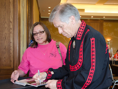 "Chief Pyle signs his photo in the photobook, ""A Cultural Awakening,"" for Pam Reeder while at the La Jolla meeting."
