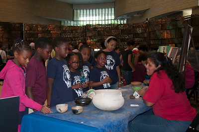 Students from the Reid Temple Christian Academy of Glenn Dale, Md., learn about traditional Choctaw pottery from Amy Thompson.