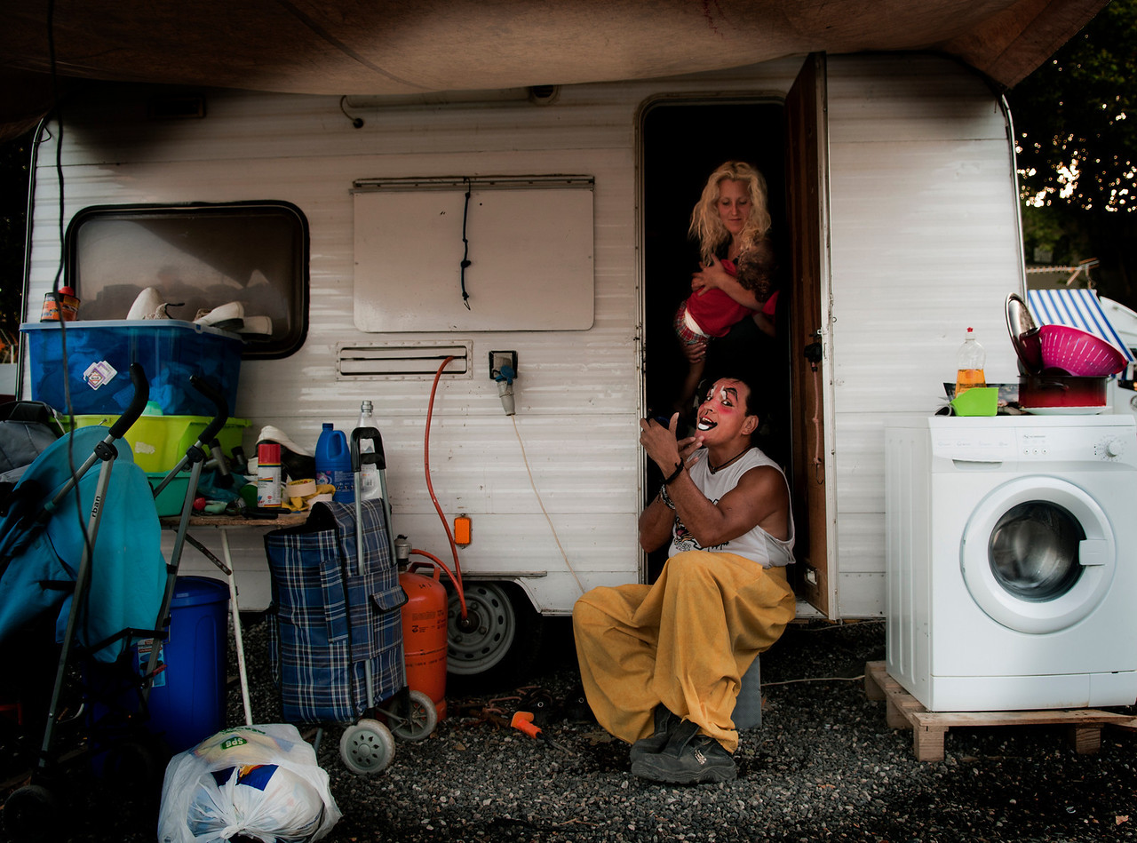 The clown puts on his make up ready for another show. His wife stays behind in the small caravan putting there youngest child to sleep.