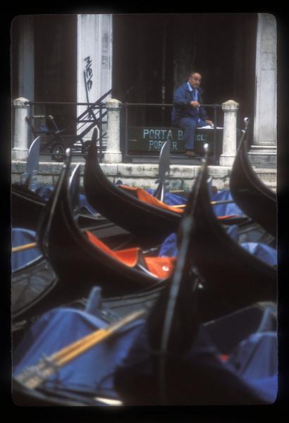 Gondolas and resting man, Venice, Italy.