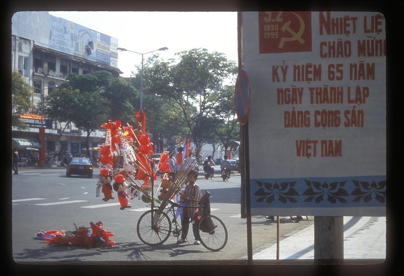 Balloon vendor and Communist slogans, Ho Chi Minh City, Vietnam.
