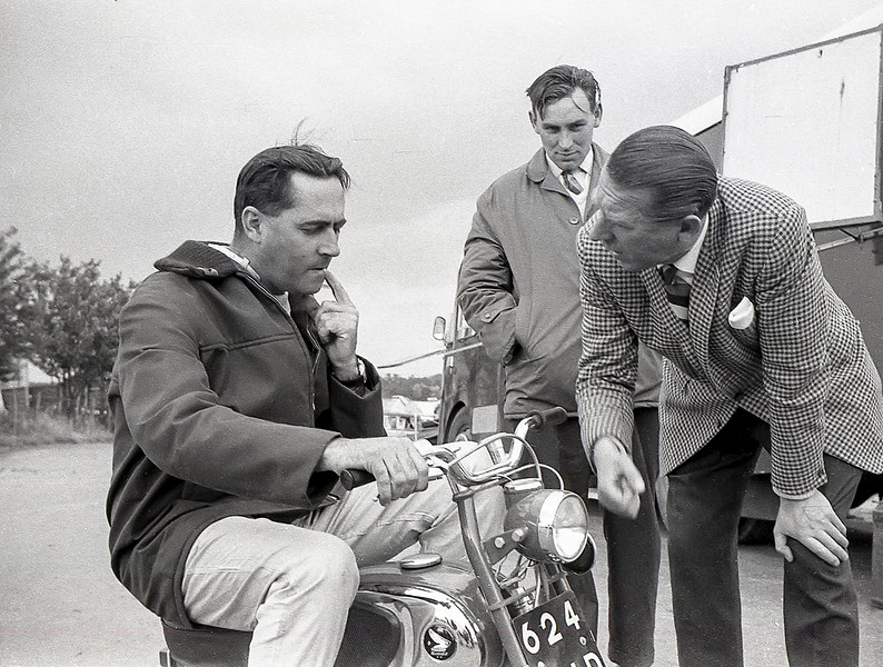 Rob Walker persuades Jack Brabham to try a micro motor bike; Trevor Taylor looks on