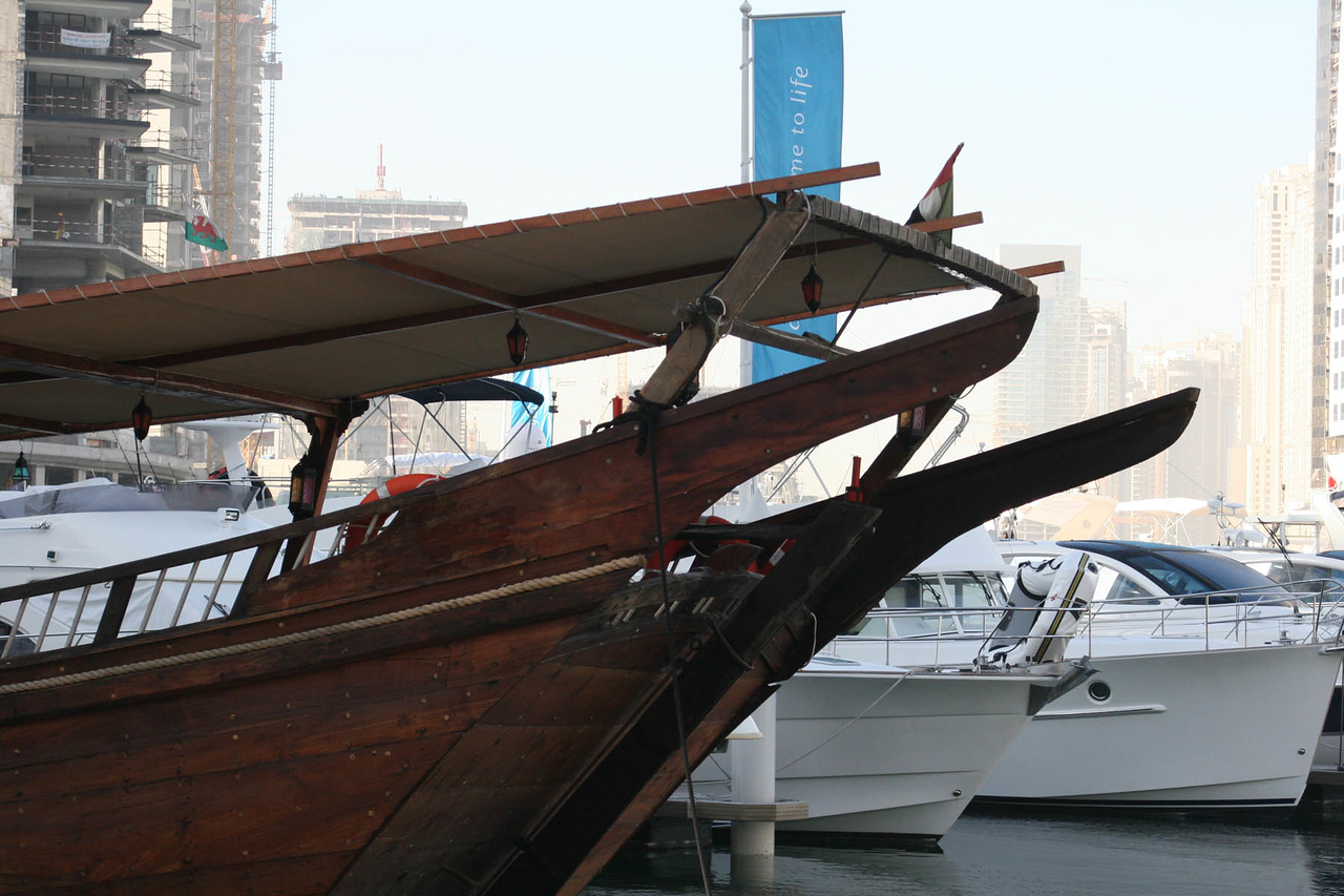 A Dhow sets next to the new yachts in Dubai marina