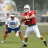 Andrew Luck looks to pass during a drill as quarterbacks coach Clyde Christensen looks on during Colts camp on Saturday.
