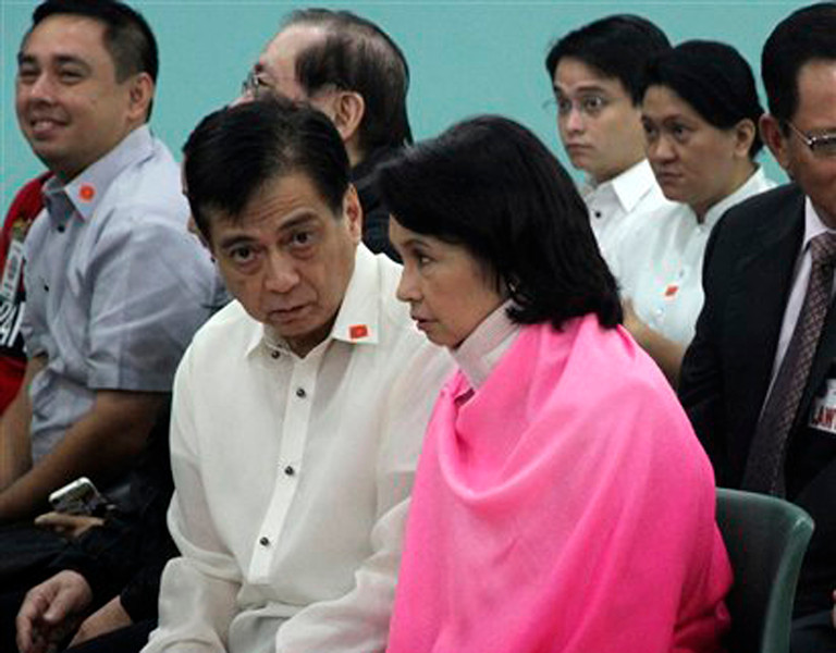 In this photo released by the Philippine National Police Public Affairs Office, former Philippine President Gloria Macapagal Arroyo, right, who is currently under hospital arrest, talks to an unidentified counsel prior to the start of her arraignment at the Sandiganbayan (Anti-graft Court) Monday, Oct. 29, 2012 at suburban Quezon city, northeast of Manila, Philippines. Arroyo, who is charged with plunder for allegedly misusing state lottery funds, refused to enter a plea prompting the anti-graft court to enter a not guilty plea on her behalf. At extreme left is her son Congressman Dato Arroyo. (AP Photo/Ernesto Lasig, Philippine National Police)