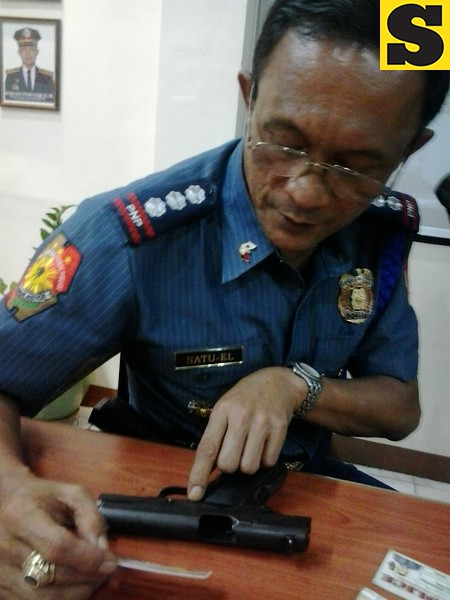 Acting Cebu City Police Office (CCPO) Director Mariano Natuel Jr.  points to the caliber 45 pistol confiscated from the suspect in the killing of a Cebu traffic enforcer. The gun is supposed to have 10 bullets but the police only confiscated seven live bullets. (Photo by Armie Garde of Sunnex)