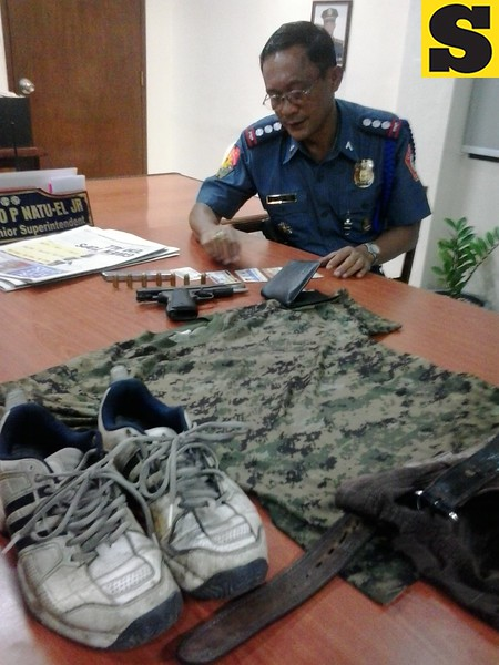 Acting Cebu City Police Office (CCPO) Director Mariano Natuel Jr.  look into the identification cards of the suspect in the killing of CITOM enforcer Armando Daligdig Thursday. (Photo by Armie Garde of Sunnex)