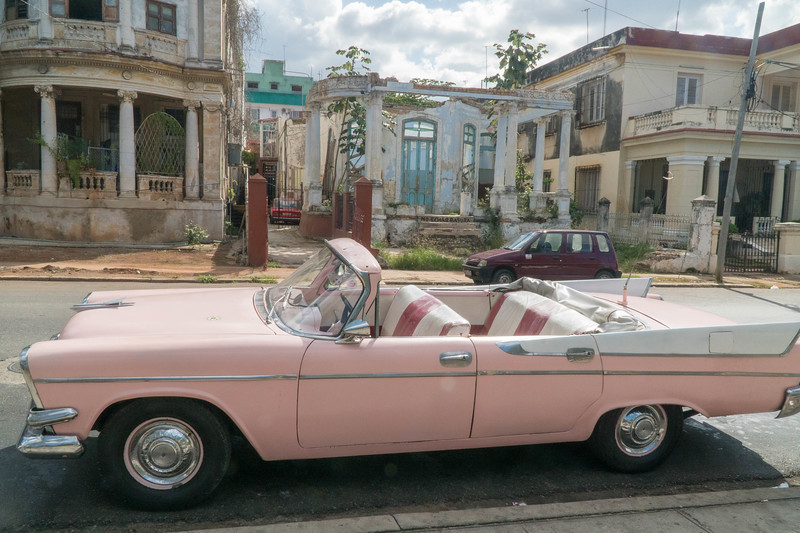 Classic car in front of collapsed building near John Lennon Park, Havana