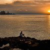 """Solitary fisherman on the Malecon, Havana. This shot composed using the """"rule of thirds"""" with the sky composing one third of the shot, the ocean another third, and the land the final third."""