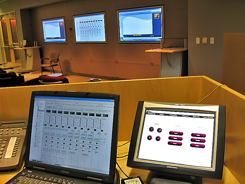The touchpanels control the lights, the shades, all aspects of the audio, video conferencing, and audio conferencing.  They also control the video matrix switcher, which gives the ability to view any source on any screen. These sources include video conferencing, DVD, VCR, a laptop from any/every podium in the room, and a number of servers from a remote server room.
