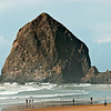Beach walkers enjoying a nice  visit to Haystack Rock.  Tillamook Rock Lighthouse is visible on far left.  It is now a columbarium.