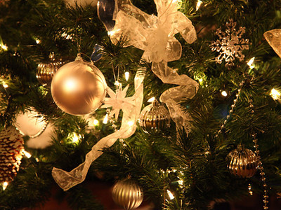 Close up of decorated Christmas tree. Focus on gold ornament on left.