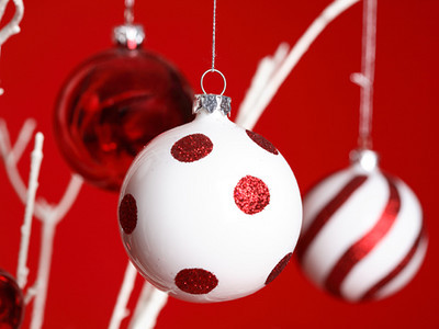 Christmas baubles hanging from white tree branches against a red backdrop - closeup. Specific focus to foreground ball.