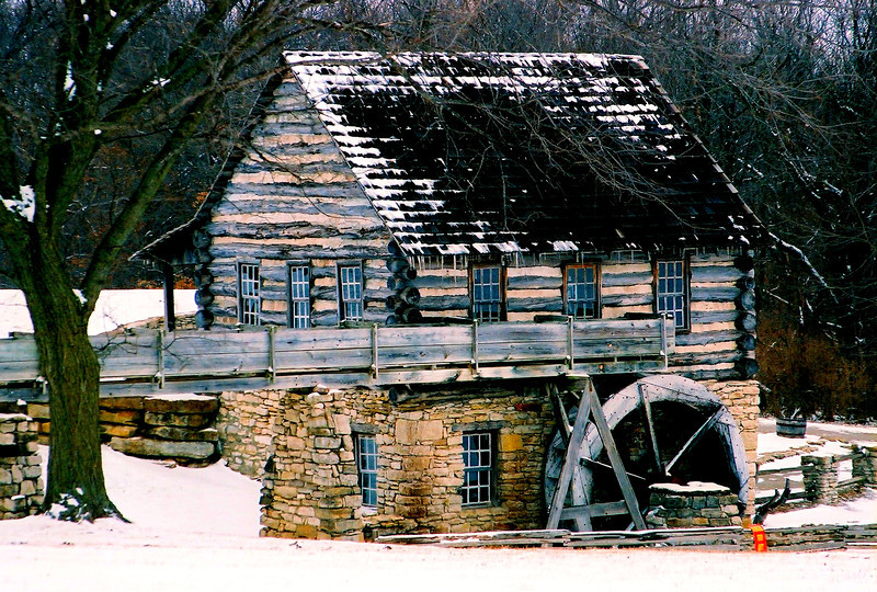 21NOV2011<br /> <br /> Fresh snow at Yankee Smith Mill.....<br /> <br />  Located in Clay County near Liberty Missouri. Yankee Smith Mill is part of the Heritage Village area of Robert Hodge Park.  It is a reproduction of a mill built on the Platte River in 1825 by Yankee Smith. The park has many buildings of the period and has a fantastic period festival worthy of your time. Grinding still occurs at the mill on certain dates and is one of the most scenic mills I have visited. This photo is one I did on the way home from Paul and Nini's last January, I was still shooting film and had this scanned and put on a disk, not nearly as good as digital.  I will get a better one next time we go see them.<br /> <br /> Your comments are so inspiring…. thanks for taking the time out of your busy day to enjoy this great mill.