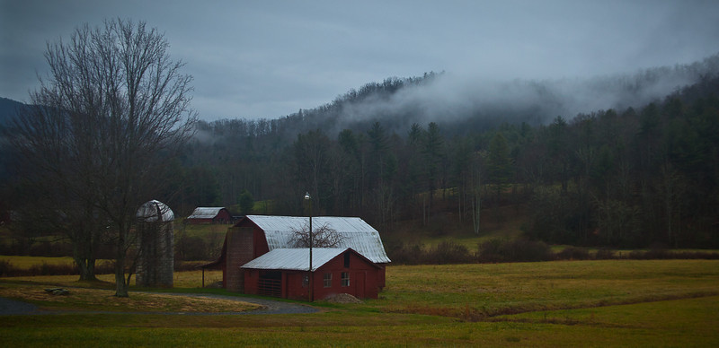 10FEB2012<br /> <br /> Rural rain......<br /> <br /> Raining heavily now we are in search of an elusive gristmill in rural North Carolina when we run across this valley of barns. The cloud deck skirting the mountainsides the rain keeps the grass a pretty shade of green and the forest floor damp and lush.