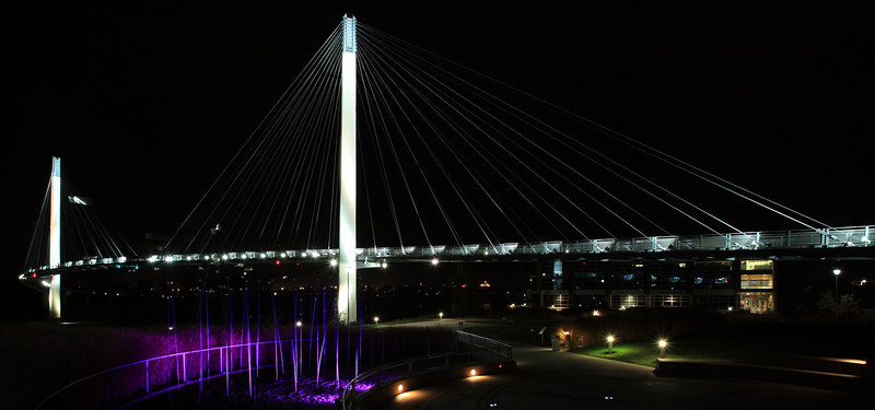 01NOV2011<br /> <br /> This is the pedestrian bridge from Omaha Nebraska to Council Bluffs Iowa. The National Park Service building sits on the south side of the bridge on the Nebraska side. This view is looking east towards Iowa. The poles coming out of the ground that are purple have glass luminating ends on them, not lit tonight. We had a hard time getting the puple lights to come on and with the high wind we had Saturday night the tops of these were swaying causing the wierd reflections between the bridge supports. You can have a fun night in Omaha, it has a lot to offer....no snow yet! Thanks Paul!