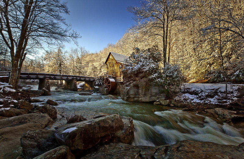 "08FEB2012<br /> <br /> First light at Glade Creek Mill......<br /> <br /> Some say this is the most photographed gristmill in America I would have to agree for the last thirty or so years. Marbry Mill has been around for a lot longer and has been documented in photos for a great while longer than Glade Creek. Glade Creek is just a stunning place to visit, great people at the Babcock State Park make this destination fun and interesting the park is beautifully kept and offers trails, bike paths, camping, fishing, kayaking any sort of outdoor recreation.<br />  <br /> The New River George area is a top tier recreation area that offers beautiful surroundings around every corner. A favorite destination for me I have visited many times in all seasons and yet it still draws me back. This is the last shot I took before my fall that broke the lens off my camera body. I am a Gristmill enthusiast and have drug my children to many many mills, often at their displeasure, I belong to the great organization called SPOOM the Society for the Preservation Of Old Mills, they can be found at  <a href=""http://www.spoom.org"">http://www.spoom.org</a>. To date I have circumnavigated America to photograph over three hundred of these gristmill sites. Most of the Gristmills today are in serious decay or in ruins, hard to believe, our American heritage goes back to the many gristmills that started most of our communities today. Gristmills were the Mall of America in its heyday they were the meeting places Americans traded goods or had their toils changed to useful and tradable commodities, for products, for consumption. These Gristmills were the engines that made America prosper and grow, if you are lucky enough to have one close by visit your heritage, help renovate these treasures before its to late.<br /> <br /> I hope someday to write a book about these wonderful American treasures that sit in your backyard, there is no image that depicts the American heritage more to me than a great image of a waterwheel on the side of a building, they normally rest near beautiful rivers and streams forgotten by their passerby's only to become dilapidated and bulldozed for that bright shinny seven eleven.....sad. Help save a reminder of Americana visit the SPOOM website, tell them I sent ya.....hope you enjoy this image of your past, Americans!<br /> <br /> For all the great folks outside America this Gristmill site rests in Babcock State Park a little north and east of Beckley West Virginia, it sits in Appalachia an area rich in American history, the New River is said to be our continents oldest river.<br /> <br /> Yes most of these mills are east of the Mississippi, SPOOM offers a directory of these sites for sale and although the directions given in them are scetchy at best remember you are looking for landmarks that have been developed around so some of the landmarks described in the directions to these places no longer exist. There have been many many tanks of gasoline exhausted in my search for  some of these gristmills only to be not even close to where they really are, thats how much the area around the mill sites have changed, enjoy your quest Barry, we have met some unbelievable people along the way to find them....most of the people that have them now are like minded of our ancestors, self motivated entrepreneurs wanting to restore American heritage for Americans....thanks for your question.<br /> <br /> I do Mills with waterwheels only......Thanks for the great info, I will pass that on! Enjoyed the story Ed.<br /> <br /> Thank you for all the wonderful comments and questions!"