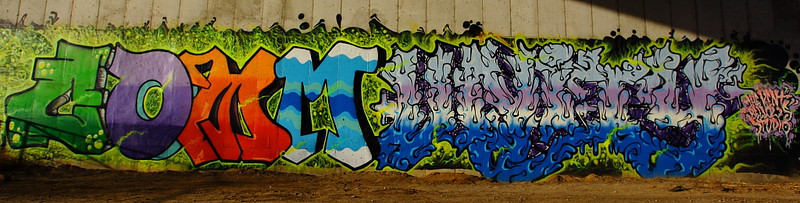 17NOV2011<br /> <br /> It's who we are....it's who we be.<br /> <br /> I shot this yesterday here in Omaha Nebraska.  This is the latest city supported graffiti art that is alongside one of the most popular trails in town, about two miles away. It is about fifty feet long and eight feet tall. We drove up to the site and by the time I had the camera on the tripod the police were driving down the road toward us, the officer explained it was art.  I let her know I was a member of the local camera club and just wanted to take a shot for our next show and tell night. <br /> <br /> Yesterday when I was processing it I had smug up behind my work and noticed the new STOP CENSORSHIP stamp over the smug insignia at the top of the daily page, ironic. It is hard to make out what word it is when you are standing in front of it. The caption  intro words are from one of my favorite Black Eyed Peas songs. Sorry for the small crop just view it large........enjoy, and let me know if you figure out what it does say!<br /> <br /> Thanks also for going back and reading yesterday's story behind the photo, all the great comments are inspiring!<br /> <br /> OK a few hints....if you sit back away from the computer screen you can read it alot easier....and your in it now.....good luck!