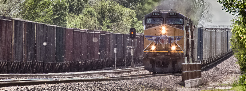 27MAY2014  Cottonwood Canyon  Out and about yesterday we went to hooker hill and shot this, 5852 is coming at me at 45 MPH with a full coal train in the siding idling.  Milepost 13 or 120th street here in Omaha Nebraska, 120th street runs under the tracks here north and south.  Watching the coal trains run…..from this location we watch them drop off highpoint hill here and descend into downtown Omaha.  Hope the Memorial Day festivities cheered you up from the memories of those who have gone before us.  Looking almost like snow falling on a calm Winter day it is 87 degrees out and very high humidity, the Cottonwood trees that line the Union Pacific right-of -way gently float till the wind comes by.  Have a great week…..please leave me a comment, thanks!