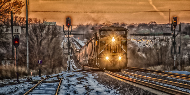 """06JAN2014  Eastbound Grains  Just coming out of the West Omaha siding 6854 heads  to Iowa from here. This train sat in the siding most of the holidays in fact i was trying to get a long distance shot of this as it sat in the siding when the crew van showed up and out came the crew. Just at sunset he got the green to move to mainline #2 into"""" Seymore"""" where I'm standing. Seymore is a place near by where i live and the sunset here are awesome as well…..however a bit cold. I think they knew i wanted a image…..it took them forty five minutes to cross the switch and get to this point, lol….frozen!  Our airport and the trains are the only things moving outside…..the train crew that works West Omaha were sitting here this morning at -16 below zero waiting for the green to get track #2 westbound. My equipment is hard to hold its so cold.  Thanks for taking the time to look at my Images! Please leave me a comment."""