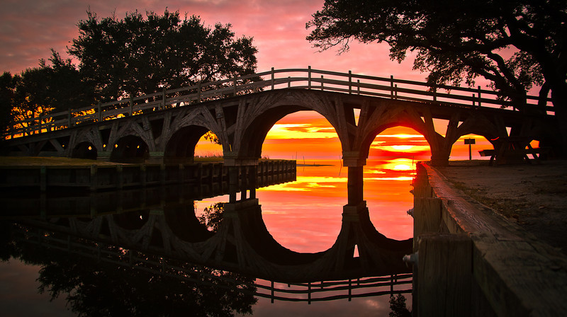 31DEC2011<br /> <br /> Sunset bridge...<br /> <br /> Found this in a park next to the Currituck Beach Lighthouse, take time to stop here this was one of the most scenic sunset's i have witnessed for a long time, Blue heron's, cranes, geese, a whole plethora of waterfowl show up here. Three miles north is the Currituck National Wildlife Refuge home of cape's wild horse population. The area is also known for great seashell gathering and Kill Devil Hills is just twenty miles south. This would be a place to bring your paddle craft i saw many photo op's just off the shoreline that would have been awesome provided the temperature was acceptable.<br /> <br /> Thanks for all the great comments, wishing all a Happy New Year. #1 Dec. 31st 2011 Thanks go out to Paul Jr. who forces me to get better....Linda who shows me the direction even if it is the internationally known i'm # one sign....Linda's great without her these pictures don't get to you.... the also great DAILY community, thanks for looking hope to see you out on the trail and in the backcountry this year.....let me know how i can help you get there!