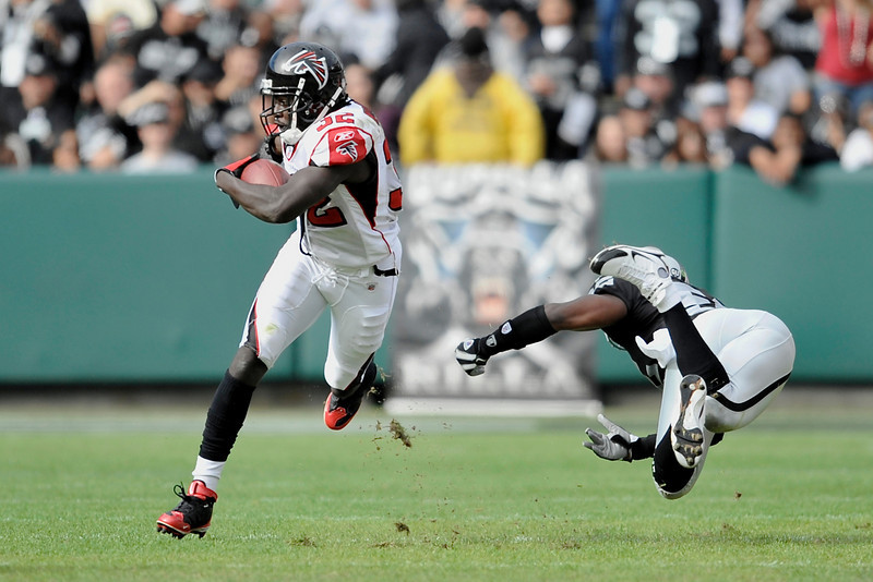 Nov. 2, 2008; Oakland, CA, USA; Atlanta Falcons running back Jerious Norwood (32) sprints past a diving Oakland Raiders linebacker Kirk Morrison (52) during the first quarter of the Falcons game against the Raiders at Oakland-Alameda County Coliseum in Oakland, CA. Mandatory Credit: Daniel R. Harris-US PRESSWIRE