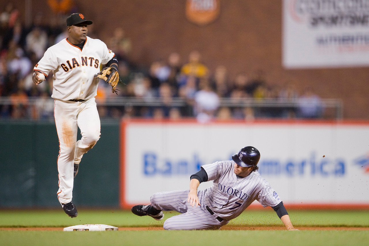 14 September 2009:  San Francisco Giants third baseman Juan Uribe (5) leaps to avoid Colorado Rockies left fielder Seth Smith (7) sliding hard to break up a double play during the Giants' 9-1 win over the Rockies at AT&T Park in San Francisco, CA.