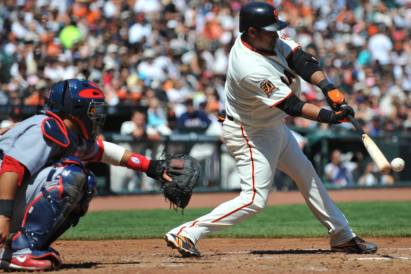 13 April 2008:  Bengie Molina drives the ball while his brother, Cardinals catcher Yadier Molina holds out his glove during the San Francisco Giants' 7-4 victory over the St. Louis Cardinals at AT&T Park in San Francisco, CA.