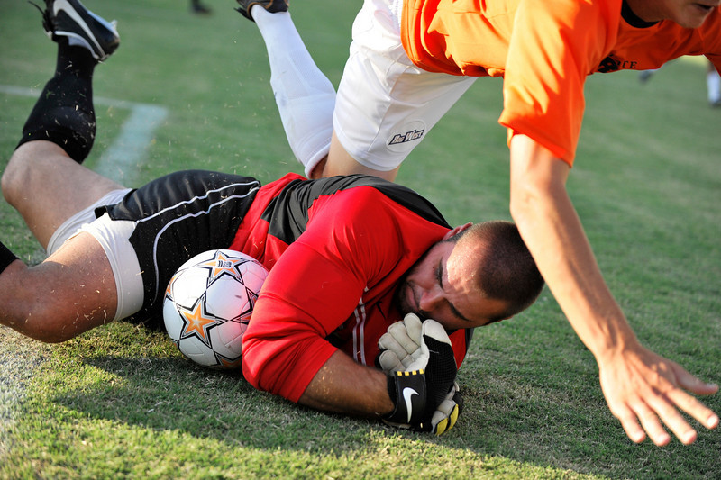 05 September 2008: UNLV goalkeeper Hawk Mummey (red) makes a diving save with Fullerton's Nick Posthuma tumbling over during UNLV's 1-0 victory over Cal State Fullerton at Titan Stadium in Fullerton, CA.  Photo awarded second place in the Sportsshooter.com Boot Camp workshop.