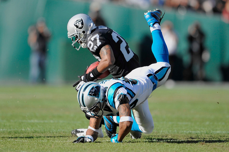 Nov. 9, 2008; Oakland, CA, USA; Oakland Raiders safety Rashad Baker (27) intercepts a pass over a diving Carolina Panthers wide receiver Steve Smith (89) during the Panthers 17-6 victory over the Raiders at Oakland-Alameda County Coliseum. Mandatory Credit: Daniel R. Harris-US PRESSWIRE