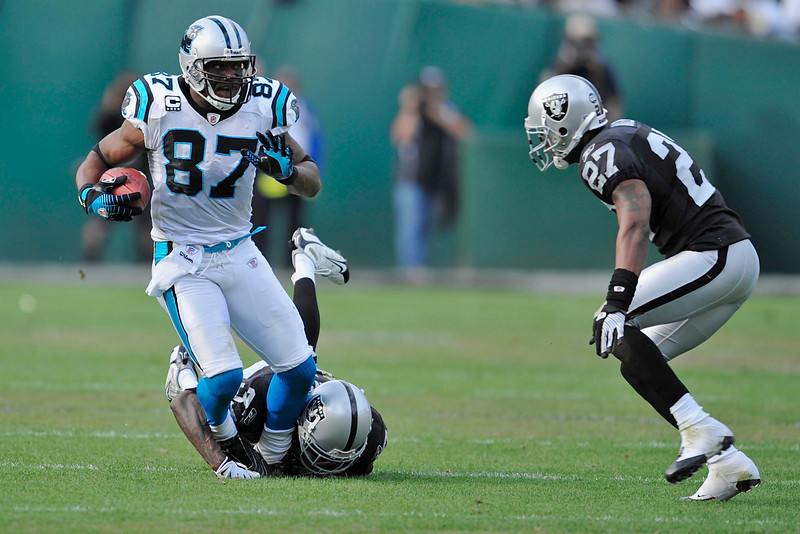 Nov. 9, 2008; Oakland, CA, USA; Carolina Panthers wide receiver Muhsin Muhammad (87) makes a catch on the run as Oakland Raiders cornerback Chris Johnson (37) dives for a tackle during the Panthers 17-6 victory over the Raiders at Oakland-Alameda County Coliseum. Mandatory Credit: Daniel R. Harris-US PRESSWIRE