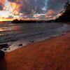 Sun bursting forth over Red Beach in Maui.  Sunrise with golden rays of sun lit up the red sand and the clouds in the sky.