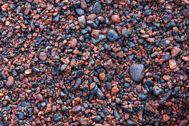 Closeup of the red and black rocks that cover Red Beach in Maui.  The beach is beautiful but these rough little rocks hurt to walk over.  All colors of red, pink, orange and black make up the unique color.
