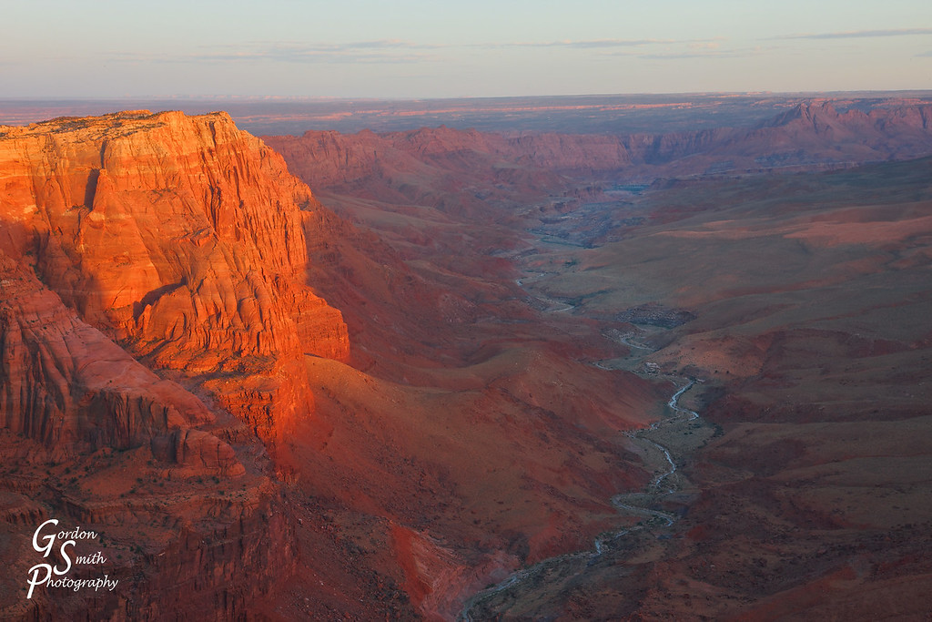 Paria River and Vermillion Cliffs<br /> Paria River meanders a thousand feet below the high canyon rim.  As the orange sun went down, the last rays spread out across the far cliff walls.  The river joins the Colorado at Lees Ferry in the distance.  Beauty!