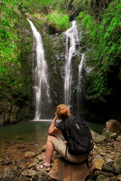 """Woman reflecting at Makamakaole Double Waterfall.  She shares the same pose as Rodin's """"The Thinker"""".  It is a great place to rest, reflect, relax and take a natural shower."""