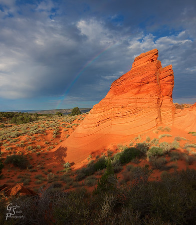 Teepee and Rainbow Paw Hole at sunrise:  you can see the faint rainbow in the sky arching over the sandstone teepee.