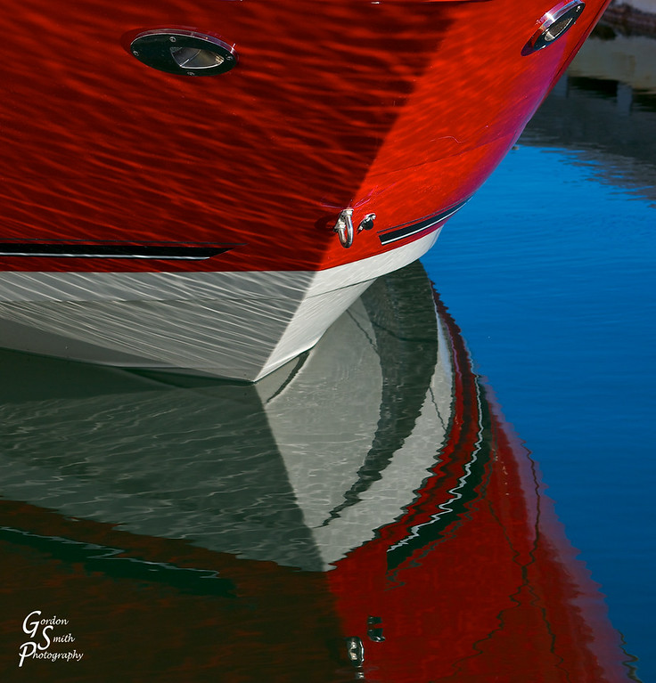 Red and White Bow of a boat reflecting in the morning light.