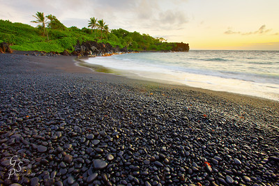 Sunrise at Black Sand Beach, Maui Beautiful reflected light from the rising sun off the black rocks and pebbles brought the black sand beach to life as waves and palms trees mingled in paradise.