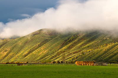 """1/5 - """"Morning Sunlight in Jackson Hole""""  I captured this outside of Jackson Hole.  The clouds were clearing and little bursts of sunlight were beaming through.  The grass was so vibrant and green from the spring rains.   I was really taken by the bales of hay with a little morning glow on them with the wrinkly mountains behind.  Just another amazing place I would love to be!"""