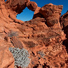 Rough Beauty<br /> Desert life extremes make even small growing bushes struggle to survive the rock terrain.  But the lovely view and arch at this location make it special to me.  This arch is un-named in the Valley of Fire state park