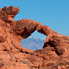 Mountain View<br /> Telephoto lens used to bring the distant mountains into view through this delicate arch in valley of fire.