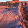 Folded Fire<br /> The Fire Wave (or Firewave) in Nevada's Valley of Fire state park lights up at sunset with reds and oranges that don't come out at other times of the day.  The rock folds back and forth on itself as if it were alive.  The sight is spectacularly beautiful