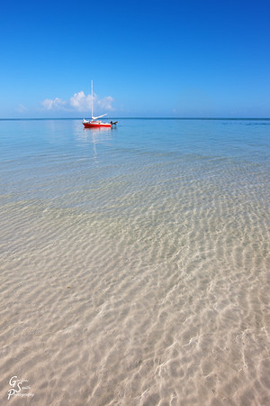 Clear Caribbean waters lead to an idyllic red sailboat floating in shallow waters.  This shot from Bahia Honda shows the small Florida Key at it's most beautiful and romantic moment.