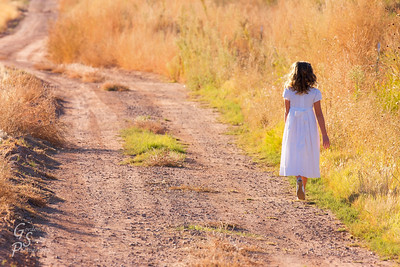Girl in white dress on a dirt road, walking by the fields