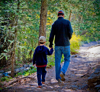 Father and son taking a early morning walk in the mountains.